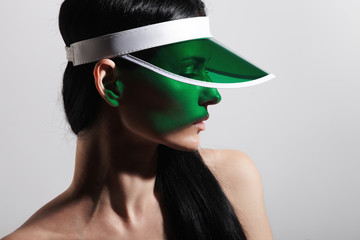 studio shoot of a woman wearing plastic visor cap