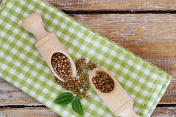 Coriander seeds on wooden scoops on checkered cloth