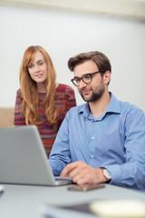 zwei junge leute schauen zusammen auf einen laptop