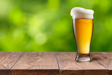Beer in glass on wooden table against green background