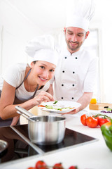 Young chef training a young attractive girl to cook