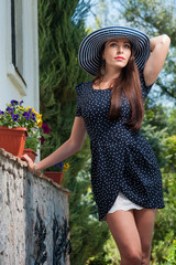 elegant girl in a summer hat outdoors