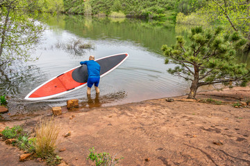 senior paddler launching  SUP paddleboard
