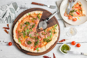Pizza with tomatoes and pesto sauce