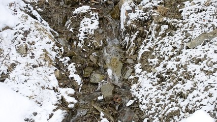 Small mountain brook flowing on stony snowy soil in winter