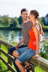 Paar sitzt auf Geländer an Fluss im Sommer