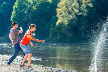 Mann und Frau flippen Steine am Fluss