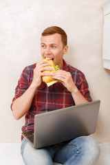 Man eating sandwich and holding notebook
