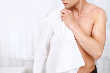 Young man putting on white shirt