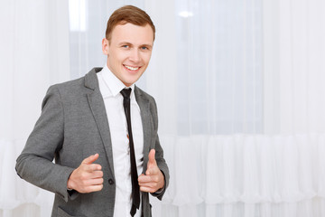Smiling man pointing with his index fingers