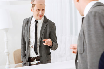 Smiling man pointing on himself in mirror