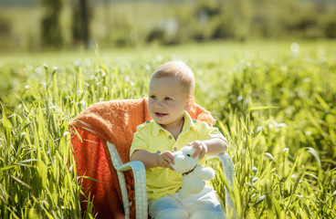 portrait of a smiling little boy on a green grass,