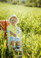 portrait of a smiling little boy on a green grass,