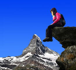Girl sitting on a rock, in the background Matterhorn