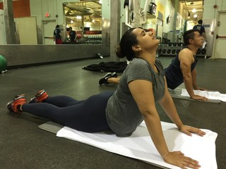 Man and woman stretching at the gym