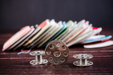 Vintage sewing machine bobbins on wooden background