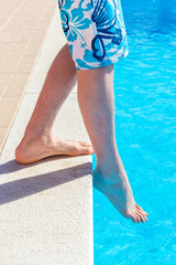 Boys legs with foot feeling water temparature in swimming pool