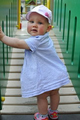 One-year-old child learns to walk on the playground