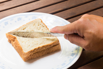 Knife slicing wholemeal sandwich bread diagonally