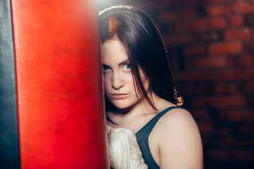 young woman boxing  posing near a punching bag in bandages