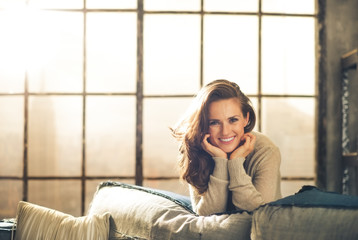 Brunette leaning over sofa smiling, resting chin on hands