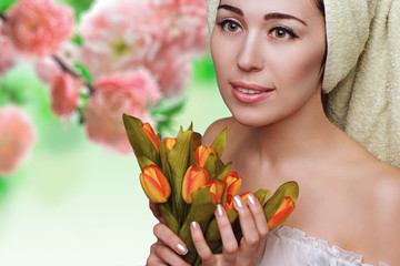 Woman in towel turban on flower background. Skin care.