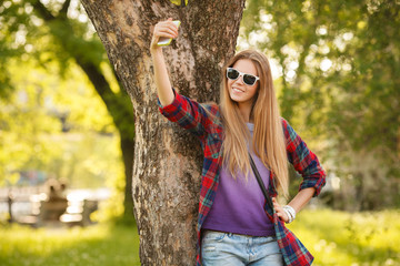 happy woman takes selfie on cell phone in summer city park