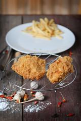 fried chicken wings with french fries on wood table.