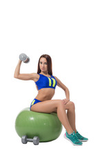 Slim brunette exercising with dumbbells in fitness