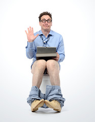 Funny man with tablet pc sitting on the toilet