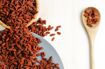 Goji berry dried in a dish, with spoon, closeup background