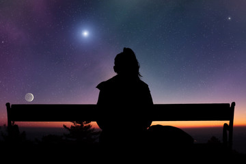 Girl watching the Moonrise on a starry skies.