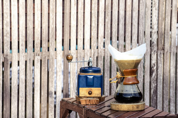 metal coffee grinder and drip glass pitcher on old wooden backgr