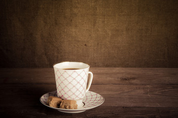 Porcelain cup of coffee with toffee on old wooden table against