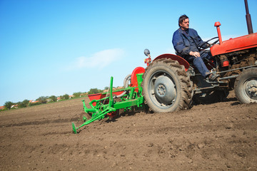 Farmer in  Old-fashioned tractor sowing crops at field