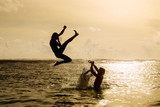 Silhouette of young woman jumping out of ocean