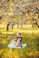 mom and little girl sits in a blooming garden