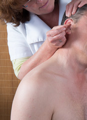 Woman acupuncturist prepares to tap needle around ears of man