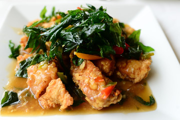 Spicy fried chicken with basil leaves on white table