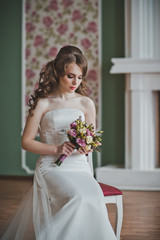 The girl in a white wedding dress sits on a chair 2669.