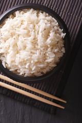 rice in a black bowl closeup and chopsticks. vertical top view