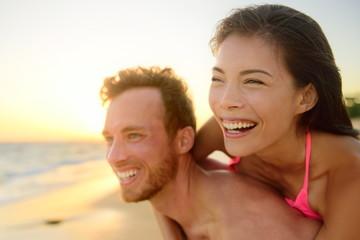 Beach couple laughing in love having fun romance