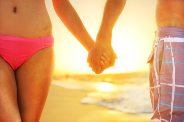 Beach sunset couple in love holding hands romantic