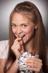 Smiling Young Woman Eating Chocolate Bar in Foil