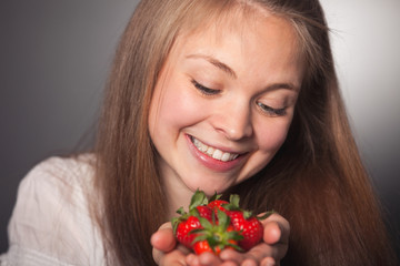 Happy Girl Looking at the Strawberries on her Hand