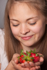 Smiling Girl Staring at Strawberries on her Hands
