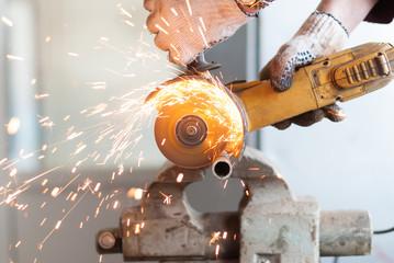 Man cuts a metal pipe.