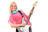 Beautiful blond woman playing a guitar and wearing blue headphon