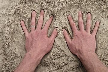 Male Caucasian hand in the salt sand on the beach.