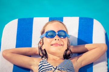 Funny child lying on beach bed